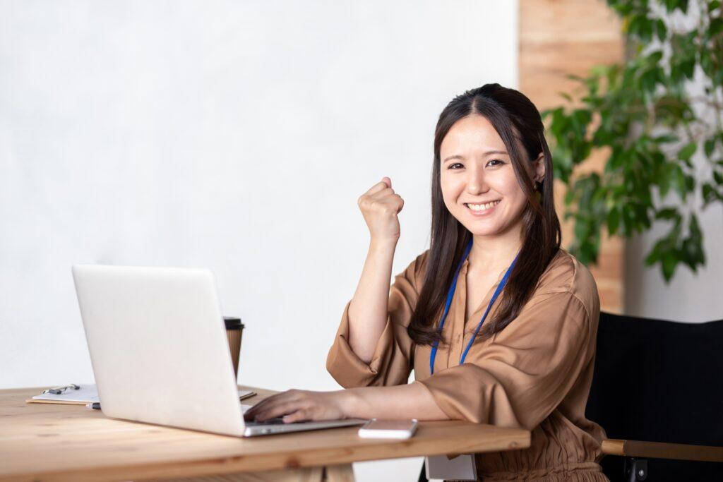 パソコンの前でガッツポーズをする女性